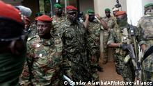 10.9.2021, Conakry**** Guinea's Junta President Col. Mamady Doumbouya, centre, is heavily guarded by soldiers after a meeting with ECOWAS delegation in Conakry, Guinea Friday, Sept. 10, 2021. The junta that seized power in Guinea has ordered the central bank to freeze all government accounts in an effort to secure state assets and preserve the country's interest and comes as a delegation of West African officials from the regional economic bloc known as ECOWAS arrives Friday in Guinea's capital, to meet with the military officers who toppled President Alpha Conde. (AP Photo/ Sunday Alamba)