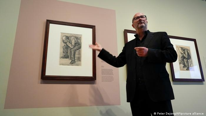 Museum researcher Teio Meedendorp points to the framed drawing with a similar drawing visible on the left
