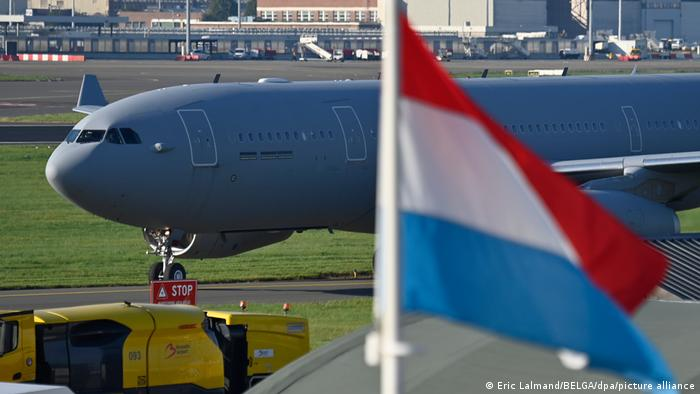 An Airbus A330 carrying evacuees from Afghanistan with a flag of the Netherlands in the foreground