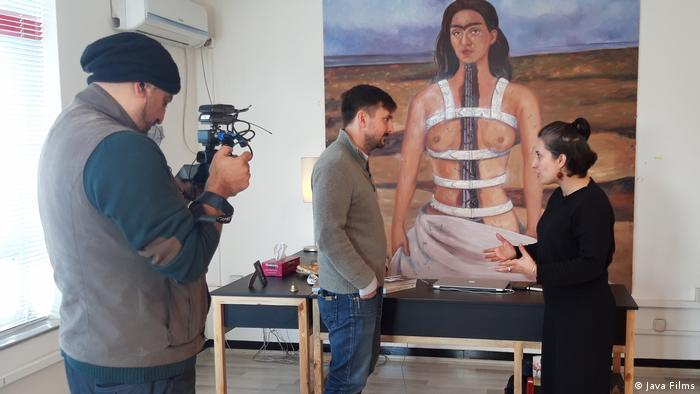 Still from 'The Ghosts of Afghanistan' a man is talking to a woman while they are filmed by a third person, in the background is a self-portrait of Frida Kahlo showing her breasts.