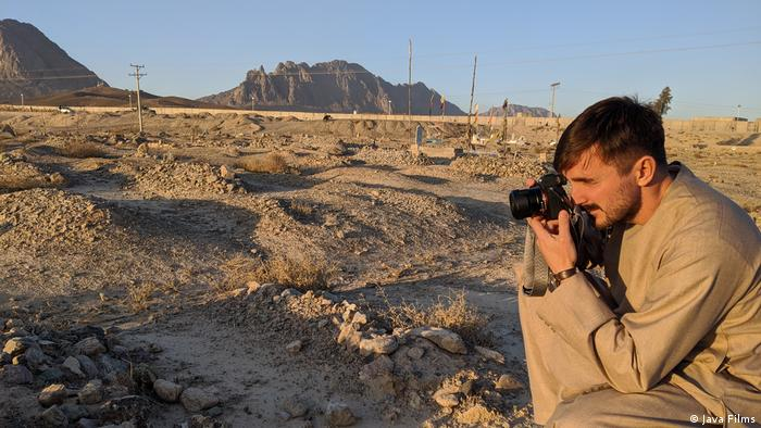 Still from documentary 'Ghosts of Afghanistan': A man taking photos in a desert landscape which serves as a graveyard.