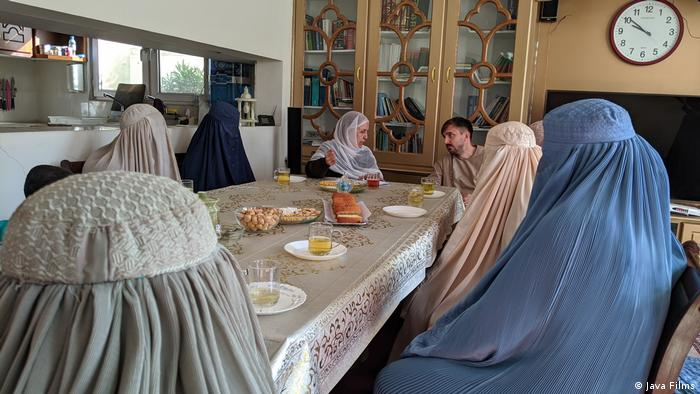 Still from the movie 'Ghosts of Afghanistan', women wearing a burqa sitting around a table and drinking tea, a woman wears only a veil and chats with a man at the end of the table.