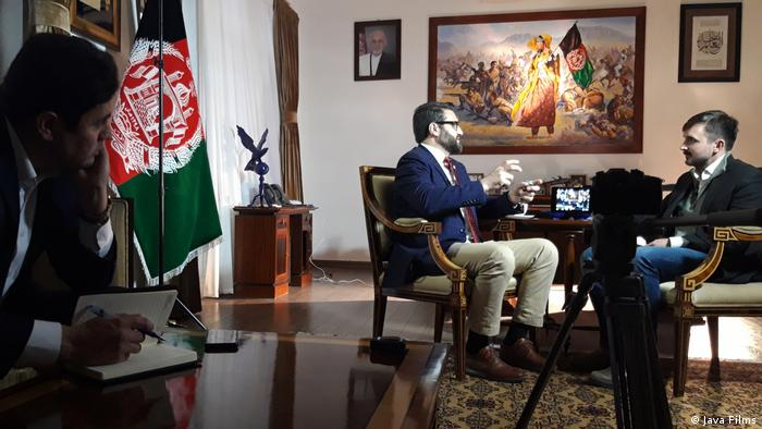 From the film 'Ghosts of Afghanistan': National Security Advisor Hamdullah Mohib interviewed by Graeme Smith, a man taking notes on the sidelines.