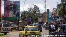 Cars drive past posters of Military junta Col. Mamady Doumbouya, on the street in Conakry, Guinea Tuesday, Sept. 14, 2021. Guinea's junta is expected to face more pressure to set a timeframe for new elections Tuesday as the military rulers open a four-day series of meetings about the West African nation's future following the president's overthrow in a coup just over a week ago. (AP Photo/ Sunday Alamba)
