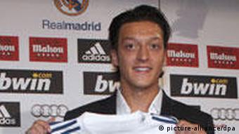Mesut Oezil holds up a Real Madrid jersey