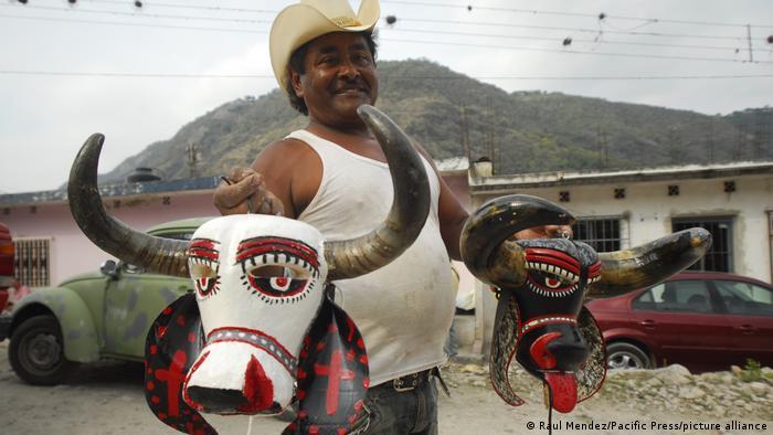 Hombre sostiene dos máscaras de Carnaval africanas.