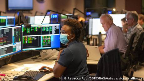 Mulher e homens idosos diante de monitores de computador