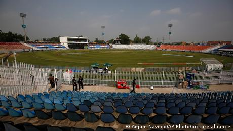 Pakistani police officers stand guard an enclosure of the Pindi Cricket Stadium