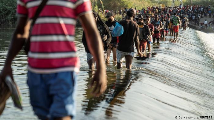 Migrants cross a shallow river