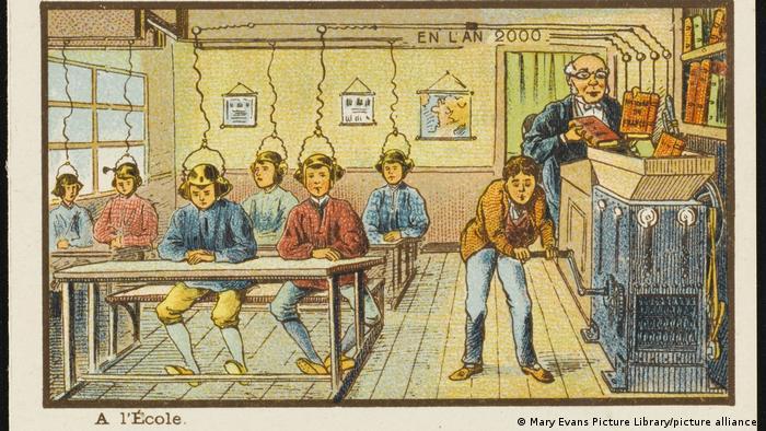 El profesor carga los libros en una tolva y los conocimientos llegan a las cabezas de los jóvenes a través de unos cables que llevan a unos auriculares. Lamentablemente, un chico no recibe ningún conocimiento porque tiene que girar la manivela.