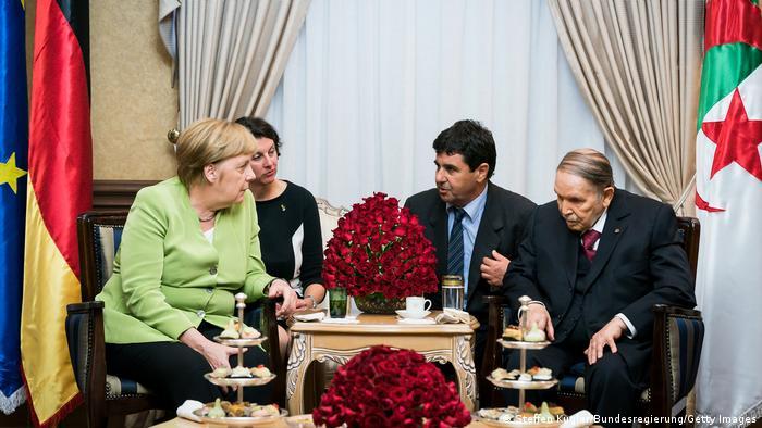 Merkel und Bouteflika und weitere Personen sitzen an einem geschmückten Tisch