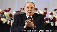 FILE - In this April 28, 2014 file photo, Algerian President Abdelaziz Bouteflika, sitting in a wheelchair, applauds after taking the oath as President in Algiers. German Chancellor Angela Merkel has called off a trip to Algeria at the last minute because long-ailing Algerian President Abdelaziz Bouteflika is too sick to meet her. (AP Photo/Sidali Djarboub, File)