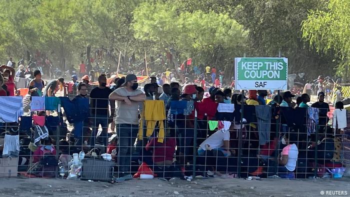 Мігранти стоять біля мосту між Мексикою та США
