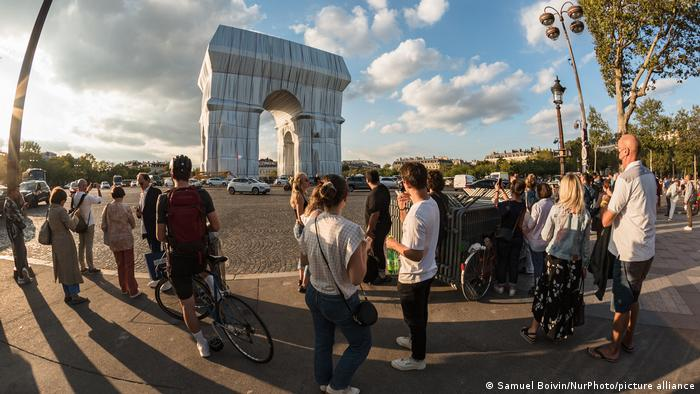 Wrapped Arc de Triomphe, people standing around the monument in den sun