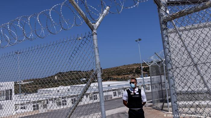 Ένας ιδιωτικός φύλακας στέκεται μπροστά από μια πύλη καλυμμένη με συρματοπλέγματα.