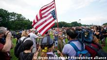 A woman holds an upside down American flag as she speaks with members of the media before a rally near the U.S. Capitol in Washington, Saturday, Sept. 18, 2021. The rally was planned by allies of former President Donald Trump and aimed at supporting the so-called political prisoners of the Jan. 6 insurrection at the U.S. Capitol. (AP Photo/Brynn Anderson)