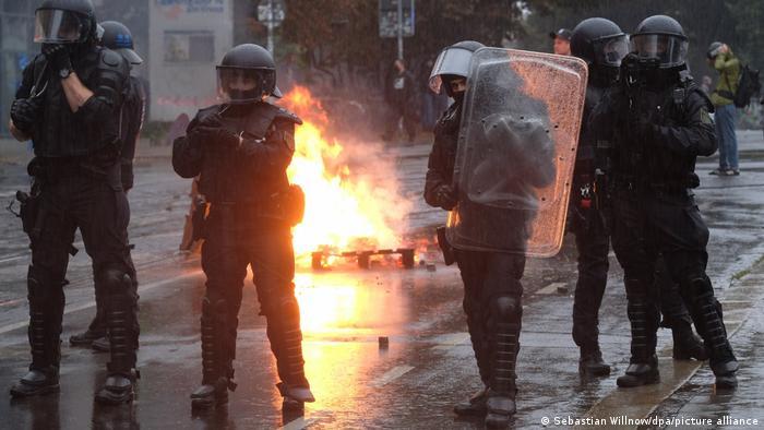 Polizeikräfte in Schutzmontur stehen vor einer brennenden Euro-Palette