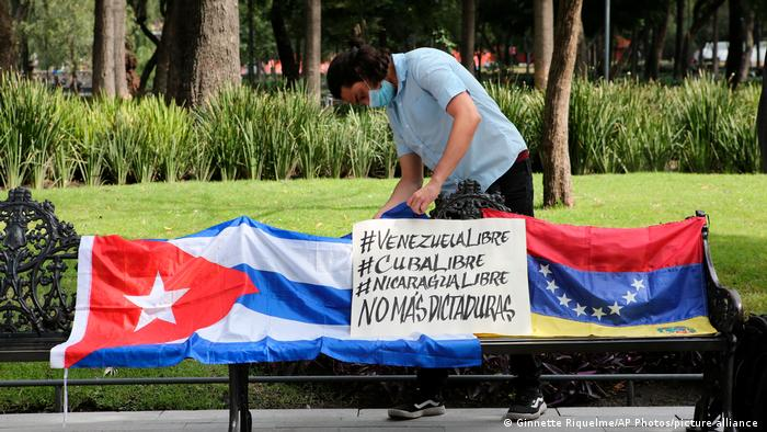Ativista põe bandeiras de Cuba e Venezuela em banco de praça durante protesto