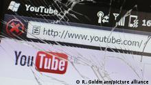 Ein defektes Smartphone des Herstellers HTC mit gesplittertem Display und der Homepage des Videoportals YouTube - YouTube ist ein Internet-Videoportal der Google Inc. mit Sitz in San Bruno, Kalifornien, auf dem die Benutzer kostenlos Video-Clips ansehen, bewerten und hochladen können.