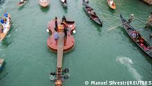 A string quartet plays onboard a violin-shaped boat, titled Violin of Noah, that was built during the coronavirus disease (COVID-19) pandemic by artist Livio De Marchi in collaboration with Consorzio Venezia Sviluppo and is dedicated to people who have died from the disease, in Venice, Italy, September 18, 2021. REUTERS/Manuel Silvestri TPX IMAGES OF THE DAY