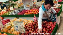 FILE - In this file photo taken Friday, April 15, 2005, a woman picks lien wu or wax apple, a Taiwanese tropical fruit, at a local fruit market in Taipei, Taiwan. China announced Saturday, Sept. 18, 2021 that it would suspend the imports of sugar apples and wax apples from Taiwan over pest concerns, months after a similar pineapple import ban was imposed. (AP Photo/Jerome Favre, File)