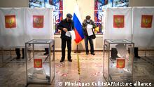 Russian citizens read their ballots at a polling station during parliamentary elections at the Russian embassy in Vilnius, Lithuania, Sunday, Sept. 19, 2021. The election is widely seen as an important part of President Vladimir Putin's efforts to cement his grip on power ahead of the 2024 presidential polls, in which control of the State Duma, or parliament, will be key. (AP Photo/Mindaugas Kulbis)