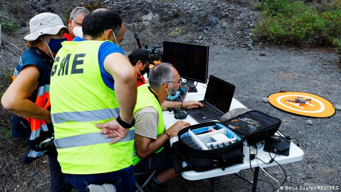 Scientists gather around a portable table in front of a drone