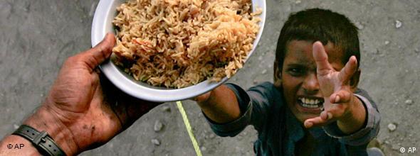 Ein Junge greift mit verzweifeltem Gesichtsausdruck nach einer Schüssel Reis (Foto:AP)