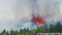 Lava and smoke are seen following the eruption of a volcano in the Cumbre Vieja national park at El Paso, on the Canary Island of La Palma, September 19, 2021. REUTERS/Borja Suarez