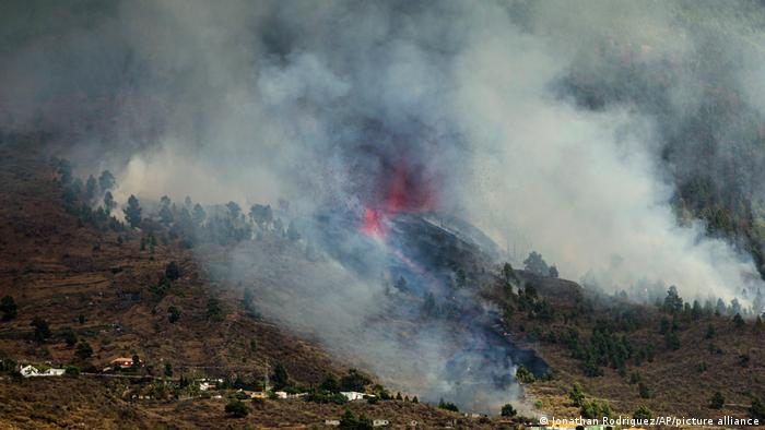 A view of smoke rising from the mountainside close to rural homes