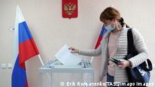 Region Rostow: Eine Frau wirft ihren Wahlzettel in eine transparende Urne