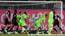 Fußball: Bundesliga, VfL Wolfsburg - Eintracht Frankfurt, 5. Spieltag in der Volkswagen-Arena. Wolfsburgs Maxence Lacroix und Wolfsburgs Torwart Koen Casteels verteidigen einen Schuss von Frankfurts Evan Ndicka (r).
