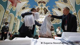 Мужчины держат избирательные бюллетени на участке на Казанском вокзале в Москве