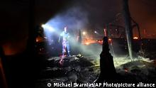 Firefighters try to extinguish the flames at makeshift tents outside the perimeter of the overcrowded refugee camp at the port of Vathy on the eastern Aegean island of Samos