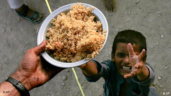 A boy receives food at a camp on the outskirt of Sukkur in southern Pakistan