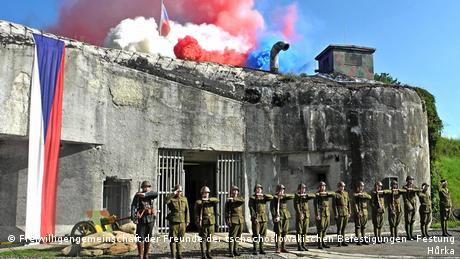 Soldiers saluting in front of a bunker with the Czech flag