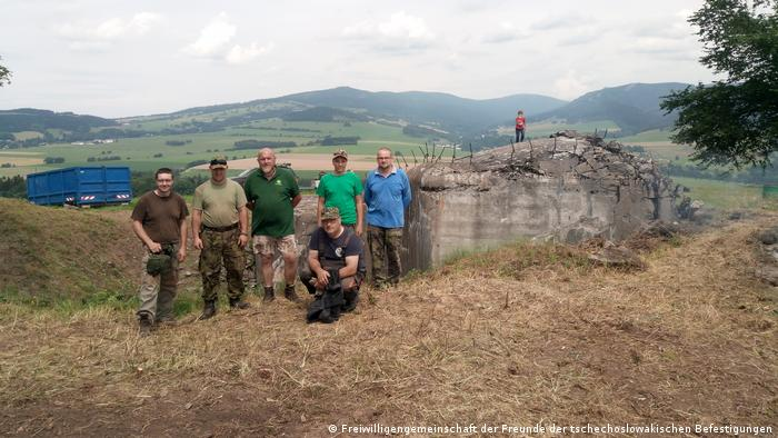 A group of men with a bunker in the background