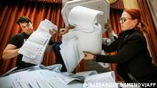 TOPSHOT - Members of a local electoral commission empty a ballot box at a polling station after the last day of the three-day parliamentary election, in Moscow, on September 19, 2021. - The vote will see lawmakers elected to the 450-member lower house State Duma, where United Russia currently holds 334 seats, and to several local legislatures. After a year that saw a historic crackdown on the opposition and with President Vladimir Putin's United Russia party floundering in the polls, authorities are doing what they can to drum up interest in parliamentary elections taking place over three days from 17-19 September, 2021. (Photo by Alexander NEMENOV / AFP)