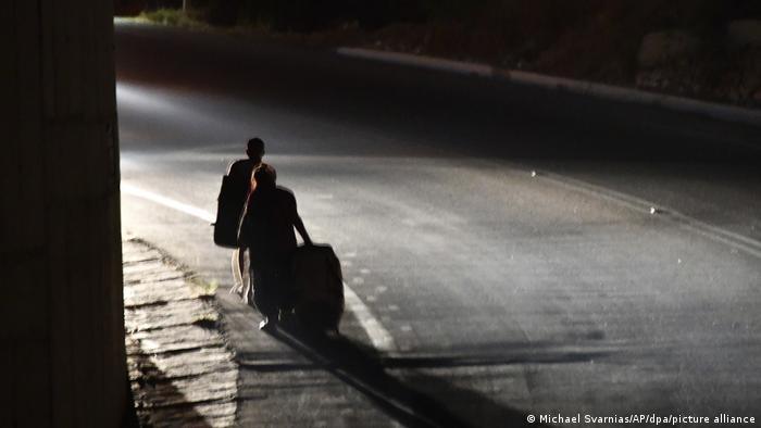 Οι μετανάστες εγκαταλείπουν το στρατόπεδο Βαθύ σε έναν σκοτεινό δρόμο.