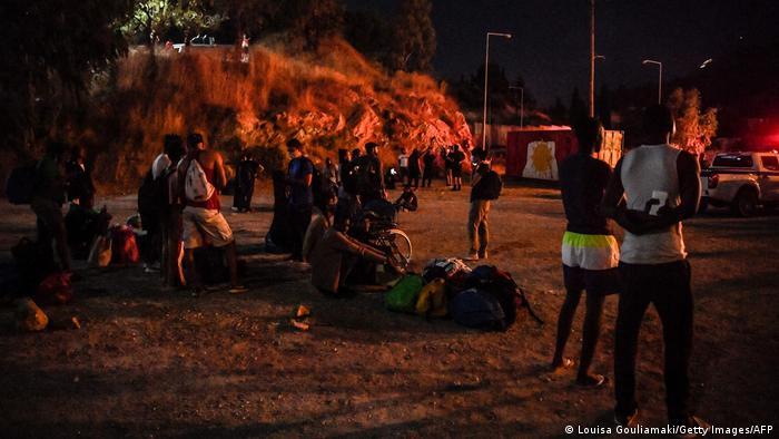 Ο κόσμος παρακολουθεί τη φωτιά να καίει σκηνές.
