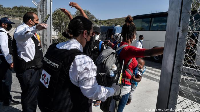 Ένας φύλακας ελέγχει έναν πρόσφυγα με έναν ανιχνευτή μετάλλων.
