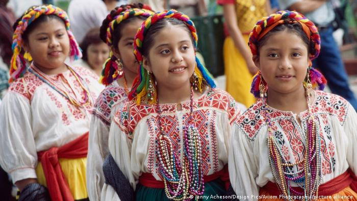 Young girls wear colorful traditional clothing with patterns in Oaxaca, Mexico.
