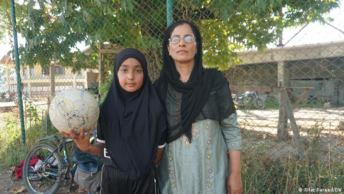 A girl holds a soccer ball with her mother