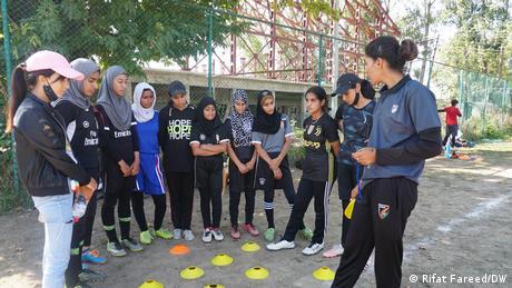 Girls gather around their football coach