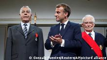 French President Emmanuel Macron, center, applauses after he honored with the legion of honor Salah Abdelkrim a former harki who was wounded, left, and general Francois Meyer who refused to execute order from above as he was a young soldier during a meeting in memory of the Algerians who fought alongside French colonial forces in Algeria's war, known as Harkis, at the Elysee Palace in Paris, Monday, Sept. 20, 2021. Macron's speech is the latest step in his efforts to reconcile France with its dark colonial past, especially in Algeria. (Gonzalo Fuentes/Pool Photo via AP)