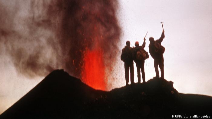 Tres hombres observan la erupción del Teneguía, en 1971.