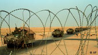 A column of US Army armored vehicles cross the border from Iraq into Kuwait