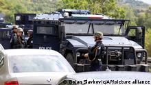 Kosovo special police with armored vehicles stand on the road near the northern Kosovo border crossing of Jarinje, Monday, Sept. 20, 2021. Tensions soared Monday at the border between Kosovo and Serbia as Kosovo deployed additional police to implement a rule to remove Serbian license plates from cars entering Kosovo, while Serbs protested the move. (AP Photo/Bojan Slavkovic)
