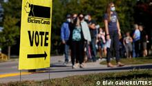 People line up outside a polling station to vote in the federal election in Bowmanville, Ontario, Canada September 20, 2021. REUTERS/Blair Gable