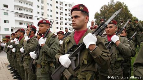 Tunisian army soldiers hold guns and stand to attention.